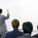 Businessman Writing on Whiteboard --- Image by © Royalty-Free/Corbis